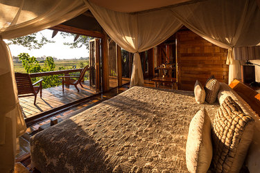 Sun drenched canopy bed looking out into the open landscape at Jao Camp in Botswana, Africa