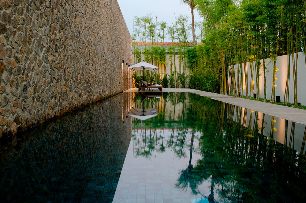 The Lap Pool with stone and bamboo walls at Amansara in Cambodia