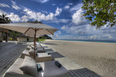 Lounger chairs on East beach of North Island in Seychelles