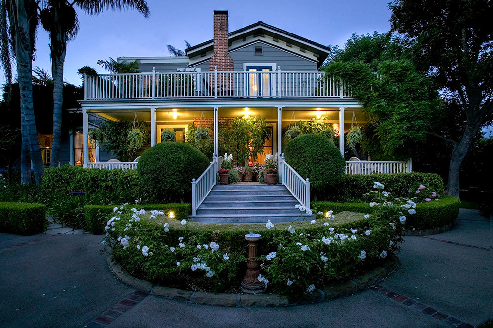 Exterior facade of the Simpson House Inn after sundown in Santa Barbara, California