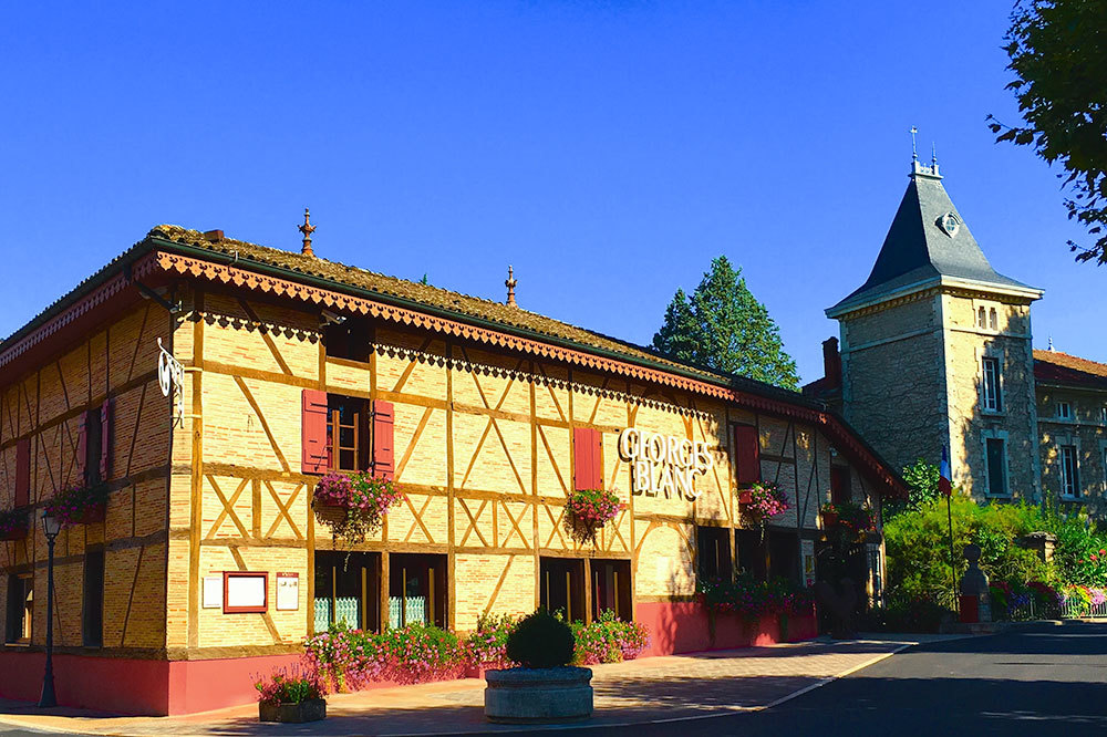 The sunny facade of the George Blanc Parc & Spa in Beaujolais, France
