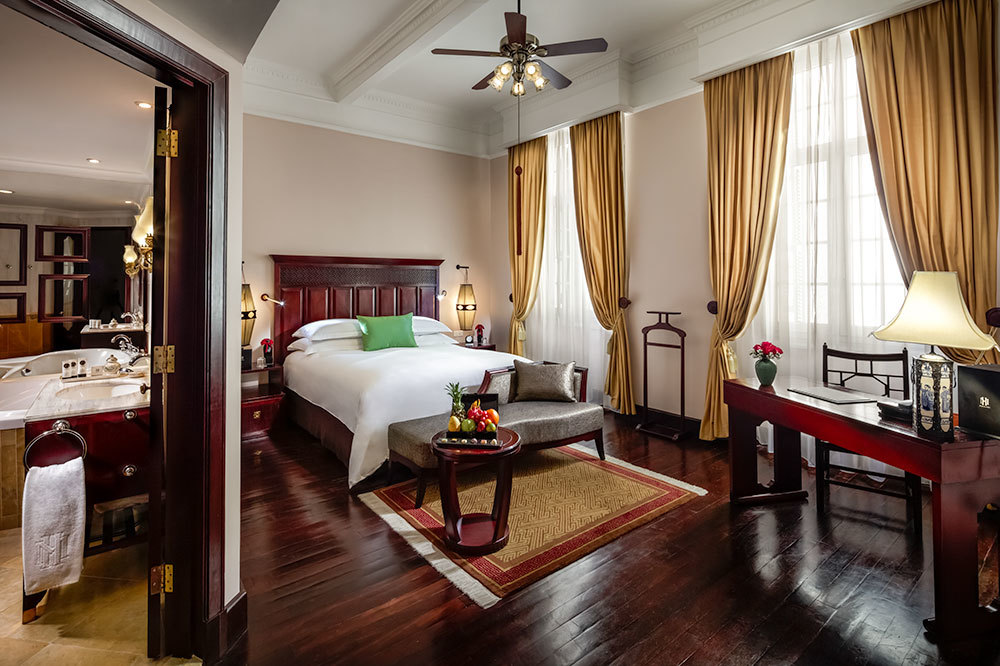 View of bed and bath of a Historical Wing Luxury Room at Sofitel Legend Metropole in Hanoi, Vietnam