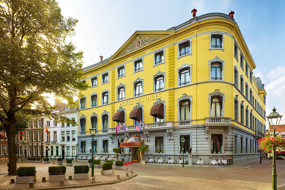 The brilliant yellow exterior of Hotel Des Indes stands out on the corner in the Hague, Netherlands