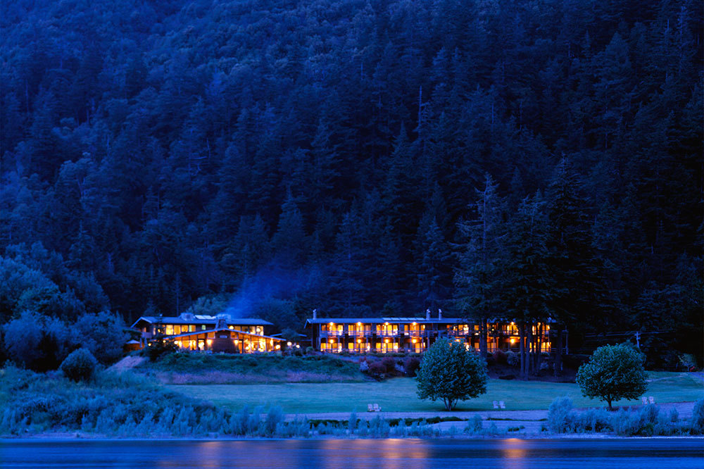 Exterior at night from across the river of Tu Tu' Tun Lodge in Western Oregon