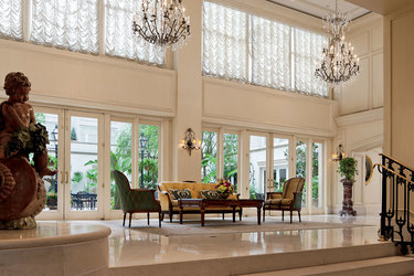 Sunlit corridor and seating looks onto patio at The Ritz-Carlton's Maison Orleans in New Orleans, Louisianain