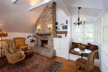 Living room with stone fireplace at Abbeywood Cottage in Simpson House Inn in Santa Barbara, California