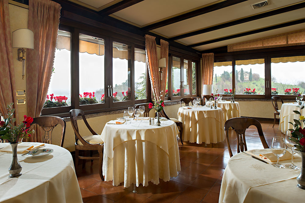 Restaurant dining room with hillside views at Hotel Villa Cipriani in Veneto, Italy