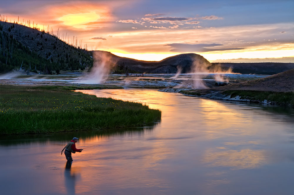 Fly fishing on the river at sunset at Firehole Ranch in Western Yellowstone, Montana
